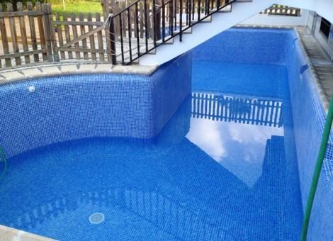 Piscina con escalera de acceso al hogar por encima de la piscina