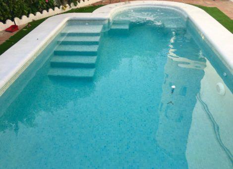 piscina con escalera de obra y spa curvo
